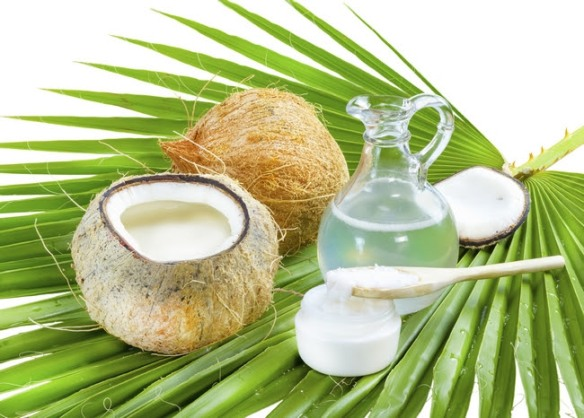 Liquid and solid coconut oil on palm leaf .